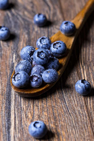 Fresh blueberries on wooden spoon. Macro shot of blueberry fruit.
