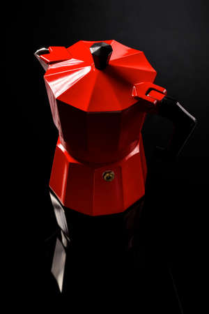 Red coffee maker mirroring on black glass background on studio shot. Stock Photo