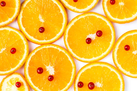 Slices of orange with red currants on top over white background.