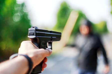 Person pointing a gun at the attacker. Auto defense concept.