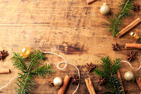 Christmas composition with anise stars, cinnamon stick and branches on wooden background. Christmas, New Year invitation, greeting card, presentation background.