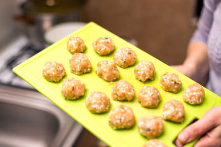 Person holding a tray  with raw meatballs in the kitchen. Raw homemade meatballs with chicken meat  ready to cook