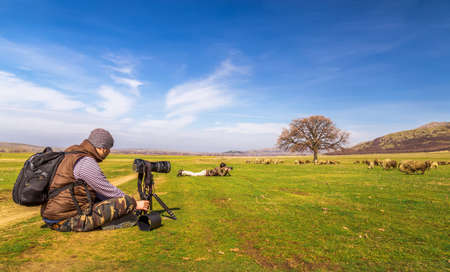 Photographers taking landscape picture on sunny day