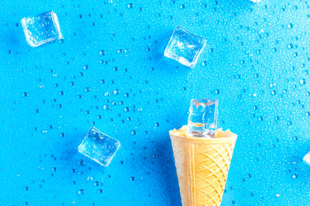 Empty ice cream cone and ice cubes on fresh blue background 免版税图像
