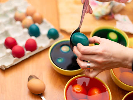 Easter Egg dying process, bowls with colored paint with eggs for painting
