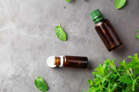 Bottles with aromatherapy oil and mint leaf. Essential oil from mint leaf. Place for text