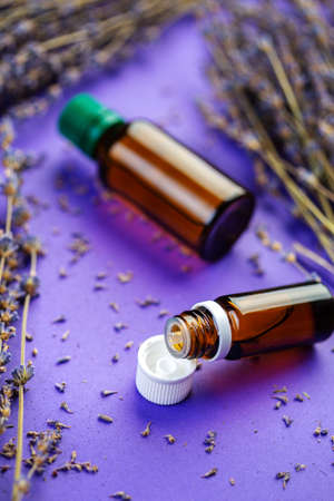 Bottles of lavandula essential oil, bunch of dried purple lavender blossom. Essential oil and lavender flowers Фото со стока
