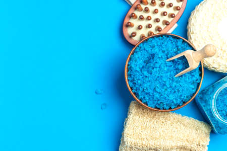 Spa setting with blue salt and sponge and copy space on blue background