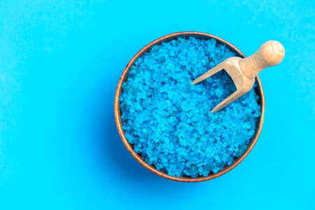 Blue bath salt and wood spoon on blue background, spa background, copy space