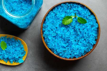 Blue bath salt on black marble background, spa setting, top view Stok Fotoğraf