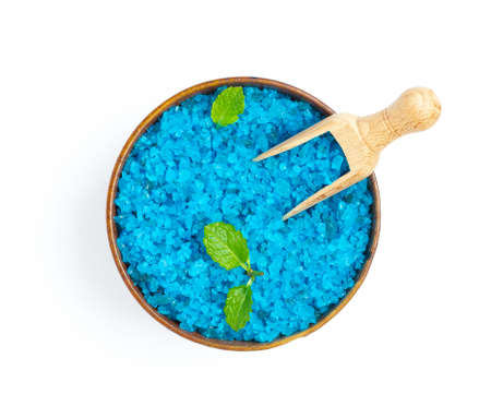 Top view of wood spoon in blue bath salt and mint leaves isolated on white background
