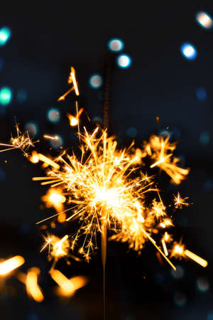 Burning sparkler with bokeh light background Фото со стока