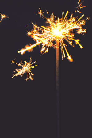 Burning sparkler on dark background.  New Year sparkles lights with copy space
