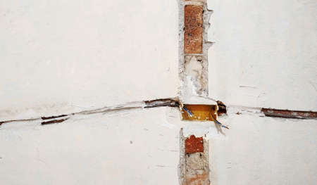 Electrical wires in the wall. Socket holes and electrical cables on the wall, renovation concept. Electrical wiring installation. Фото со стока