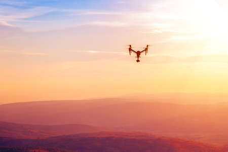 Drone flying over the hills in the sunset. The drone with the professional camera takes pictures Фото со стока