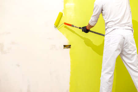 Painter use paint roller on new restored wall. Painter painting house interior Фото со стока