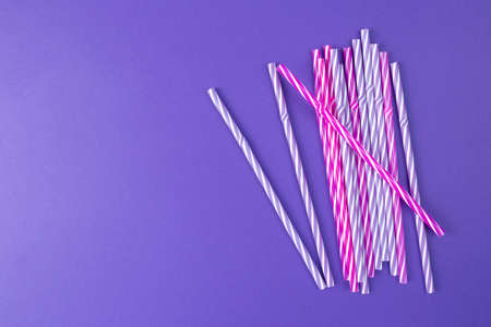 Multi Colored drinking straws on purple background with copy space. Colored tubules for juice and cocktails