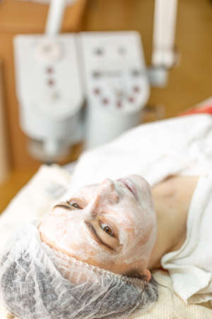 Woman with organic mask on face in spa center