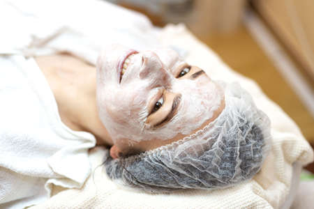Woman with organic mask on face in spa salon looking at camera