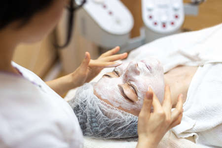 Beautician make a facial treatment in spa. Woman in mask on face in spa salon