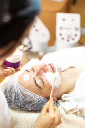 Woman getting facial care by beautician at spa salon. Cosmetologist applying mask on clients face in spa salon