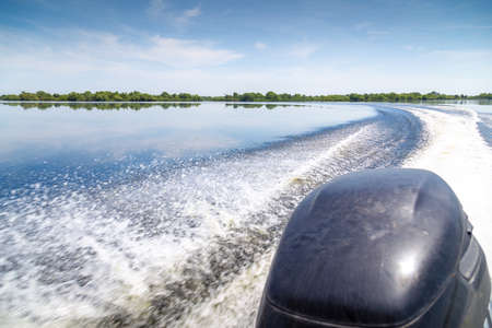Trail of beautiful water from motor boat in Danube Delta, Romania. Outboard motor closeup and trail of foam on the water. Фото со стока