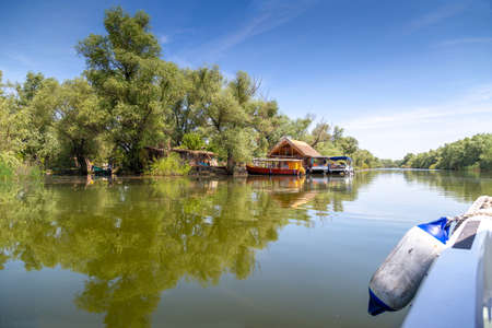 Traveling by boat through the Danube Delta. Landscape of the Danube Delta with reed huts and boats pontoons Фото со стока