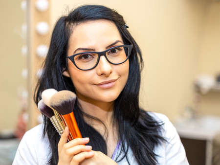 Makeup artist holding brushes. Makeover. Perfect Skin. Portrait of beautiful smiling woman with makeup brushes near her face.