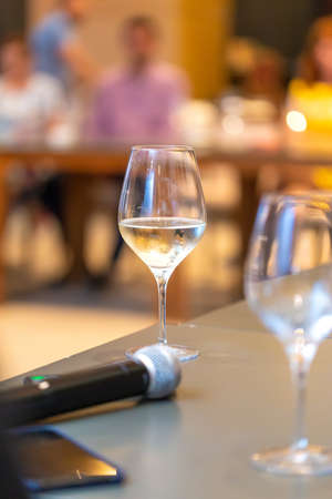 White wine glasses near the microphone on the table in a conference room. Wine tasting