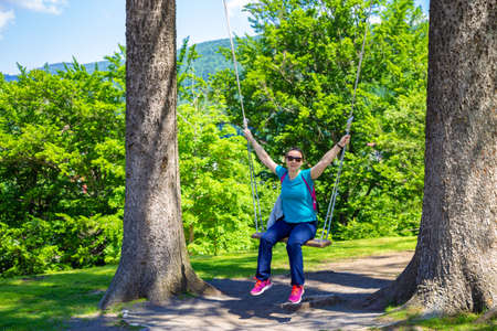 Happy woman standing in a swing between the trees