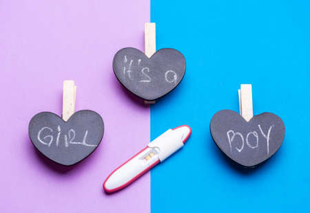 Its a Boy or girl? Pregnancy test with Its a boy or girl concept over pink and blue background concept