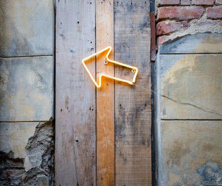 Freccia al neon luminosa su un vecchio muro Archivio Fotografico