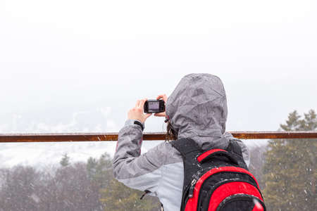Woman taking pictures with the camera on a snowy day, Place for copy-space Banque d'images - 135491682