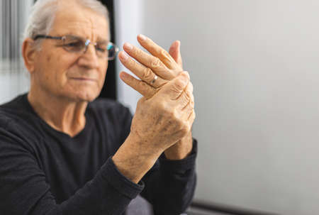 elderly person massaging his hands. Elderly Person With Painful Hand . Old man have a problem with circulation hands. Place for text