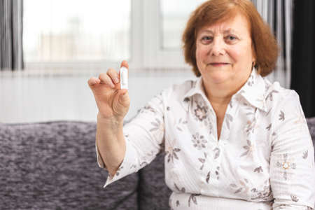 Senior lady with suppository vaginal rectal pills medicine on hand. Medical candles for treatment of candida, thrush, hemorrhoids, inflammation, vaginal and fever