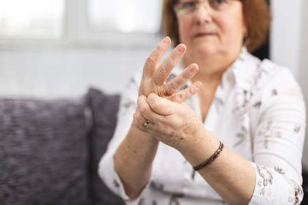 Senior lady massaging hand suffering from rheumatoid arthritis. Woman with osteoarthritis Standard-Bild
