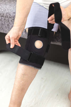 Person who puts on protective knee brace, knee support at home
