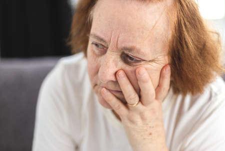 Portrait of depressed elderly woman having worries,  she worries, she thinks 免版税图像