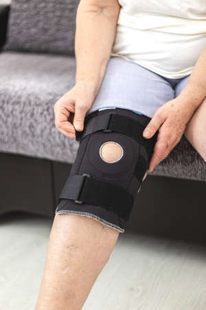 Person who puts on protective knee brace, knee support