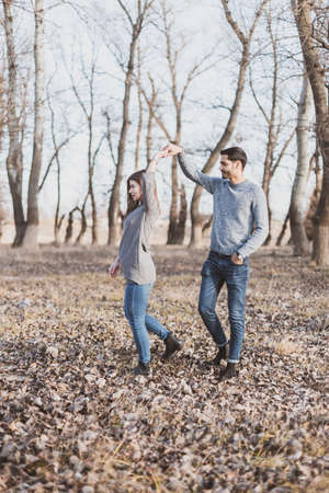 Young couple playing and dancing in the woods in the autumn season Stock fotó