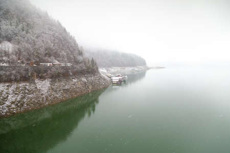 Winter snowy day in Bicaz Lake side at Mount Izvorul Dam, located in Piatra Neant, Romania