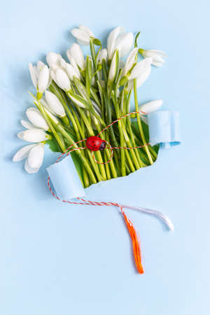 Spring greeting card made from blue torn paper with Snowdrops (Galanthus nivalis) flowers. 8 March, Martisor, Baba Marta holiday concept. Place for text