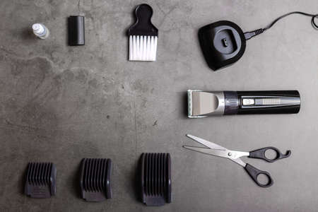 Hair clipper with accessories over black table. Place for text