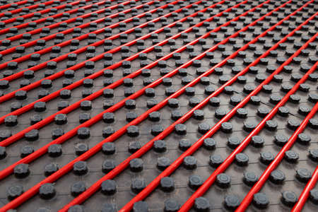 Radiant underfloor heating installation with red flexible tubing mounted on black insulation boards