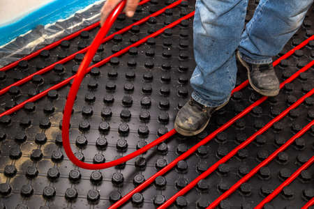 Worker who instal red tubes of radiant underfloor heating installation