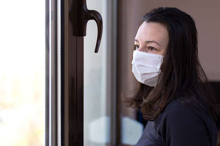 Concerned woman with mask on face in quarantine looking out window. Isolation in the house in Quarantine concept during a virus pandemic Stock fotó