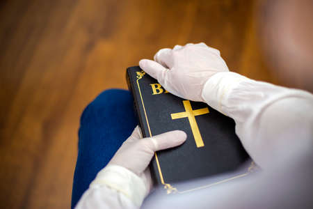 Person, nurse or doctor with mask and gloves stand in prayer with Bible in hand.  The infected person stands in prayer with the Bible in his hand