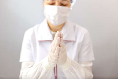 The assistant or doctor with mask and gloves stand in prayer to Almighty God.  Doctor with protective equipment making prayer gesture