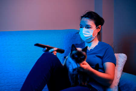 Female with mask sitting on sofa near her cat and look at tv. Concept of persona and his pet in quarantine (self-isolation)