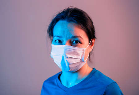 Portrait of Young Female with medical mask in studio with creative lights